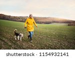 Stock photo senior woman with dog on a walk in an autumn nature 1154932141