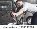 happy man touching car in auto... | Shutterstock . vector #1154947804