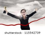 Businesswoman celebrates her winning and running through the ribbon while holding trophy - stock photo
