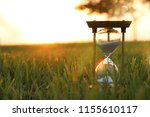 hourglass in the grass time... | Shutterstock . vector #1155610117