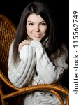 The beautiful girl in a wicker chair - stock photo