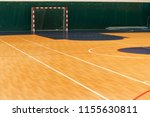 Small photo of Gym for playing futsal, mini-football. Folded wooden parquet on the field of hall for mini-football. Futsal ball and bright line markings on the floor. Floor sports hall with bright lines of marking