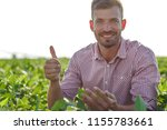 young farmer in filed examining ... | Shutterstock . vector #1155783661