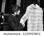 guy holds beige furry coat in... | Shutterstock . vector #1155923821