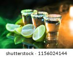 tequila and lime slices on the... | Shutterstock . vector #1156024144