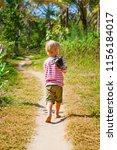 happy barefoot child walk alone ... | Shutterstock . vector #1156184017