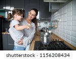 smiling mom holding cute kid... | Shutterstock . vector #1156208434
