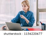 young woman working at office | Shutterstock . vector #1156220677