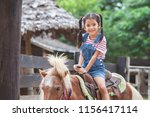 cute asian child girl riding a... | Shutterstock . vector #1156417114