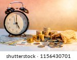 table clock and gold coin stack ... | Shutterstock . vector #1156430701