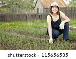 Young  woman  working at  onion plant in spring - stock photo