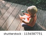 baby holding a mobile phone and ... | Shutterstock . vector #1156587751