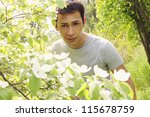 The young gardener next to a flowering quince bush - stock photo