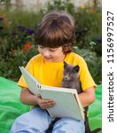 boy reading book with kitten in ... | Shutterstock . vector #1156997527