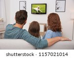 family watching tv on sofa at... | Shutterstock . vector #1157021014