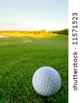 golf ball resting on bunker of lovely golf course with pale blue sky and shallow depth of field - stock photo