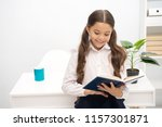 Small photo of Such interesting topic. Reading textbook. Girl child read book while stand table white interior. Schoolgirl studying textbook. Kid girl school uniform happy face read book. Excited about knowledge.