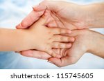 Close up of babies hand resting on mothers hand. - stock photo