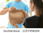 young man delivering food to... | Shutterstock . vector #1157458204