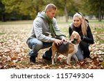 Young couple stroking dog in autumn park, smiling. - stock photo