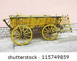 Old yellow wooden wagon standing in front of a wall of rose - stock photo