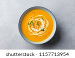 Pumpkin and carrot soup with cream on grey stone background. Close up. Top view.