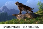 A saber-toothed cat stands atop a boulder on a grassy hill. The ferocious prehistoric predator looks down into a tree filled ice age valley rimmed with snow covered mountains. 3D Rendering