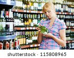 woman choosing bottle of wine in alcohol shopping mall supermarket - stock photo