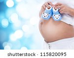 Pregnant woman holding blue baby booties, expecting boy - stock photo