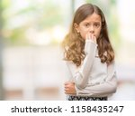 Stock photo brunette hispanic girl looking stressed and nervous with hands on mouth biting nails anxiety 1158435247