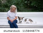 Stock photo the girl is sitting on the bench and looking at her dog 1158448774