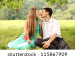 gentle kiss of a young couple on a picnic - stock photo