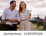 smiling couple walking outdoors ... | Shutterstock . vector #1159199224