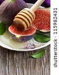 Fresh ripe figs and honey on an old wooden board. - stock photo