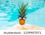 pineapple in glasses near the... | Shutterstock . vector #1159907071