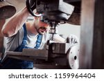 portrait of a young worker in a ... | Shutterstock . vector #1159964404