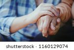 a woman holds the hand of her... | Shutterstock . vector #1160129074