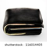 Old black wallet with credit cards and banknotes on white background - stock photo