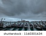 Grey Italian water city Venice and Gondola under the clouds