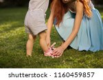 mother helps the child to wear... | Shutterstock . vector #1160459857