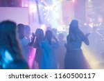 Stock photo blur light in club party show and silhouette hands of audience crowd people use smart phones 1160500117