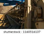 Small photo of belt conveyor to remove the empty rock from the mine goes into perspective against the background of the spoil tip