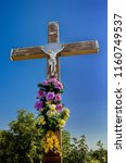 Small photo of Crucifix with flower decoration placed on the crossroad. Doggone on the crossing. For Chrissake decoration on crossway. Holy rood symbol on crossways. Rood on level-crossing with floral decoration.
