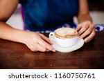cup of cappuccino in hand | Shutterstock . vector #1160750761