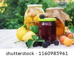 Small photo of Preserved house pears, apricots and jam with blackberries in jars. Selective focus. Food.