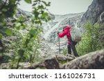High Mountain Hiker with Poles. Alpine Trailhead. Recreation Theme. - stock photo