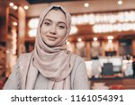 beautiful Muslim girl in hijab smiling, waiting for her food in a restaurant