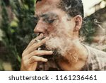 a joint in hand a man smokes... | Shutterstock . vector #1161236461