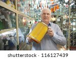 mature man holds  automotive  air filter in  auto parts store - stock photo
