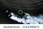 Small photo of Aerial top view two car drifting battle on asphalt street road race track, Two race car drag view from above, Car turbo drifting, Race drift car with white smoke from burning tire on speed track.